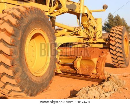 Heavy Equipment Scraping Road Top