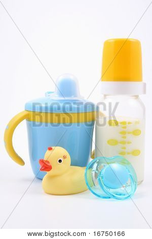 bottle of milk baby cup pacifier and yellow duck - baby stuff