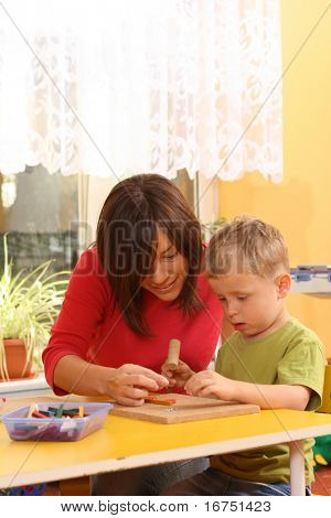 teacher and preschooler playing with wooden blocks
