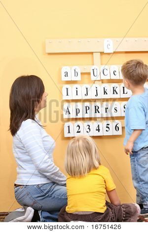 teacher and two preschoolers during lesson