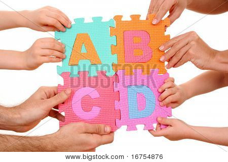 hands holding puzzle with ABCD letters isolated on white
