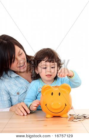 2 years old girl with her mother and piggy bank isolated on white