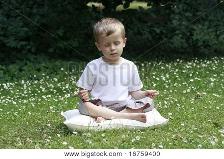 4-5 years old boy meditating outdoor