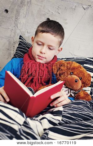 9 years old boy ill reading book in bed - kids and family