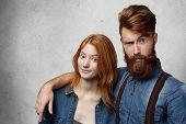 Two Young People Having Fun Together, Standing At Gray Concrete Wall. Fashionable Bearded Male Model poster