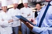 Mid section of restaurant manager using digital tablet in commercial kitchen poster