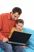 father and son having fun with computer game on the sofa