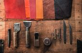 Leather craft. Well used leather craftmans tools and pieces of beautifully colored or tanned leathe poster