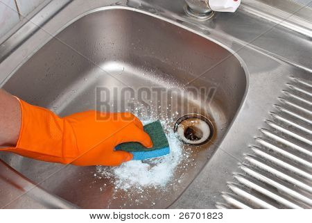 Person cleaning the kitchen sink with a glove