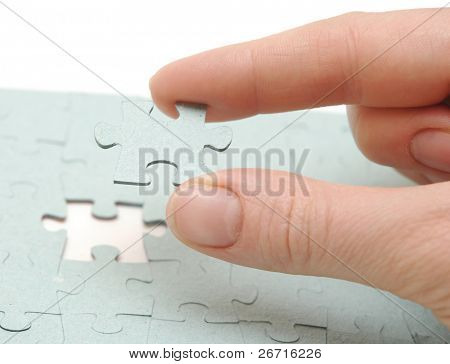 Hand inserting missing piece of jigsaw puzzle into the hole