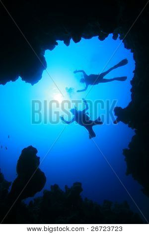 Scuba Divers descend into an Underwater Canyon