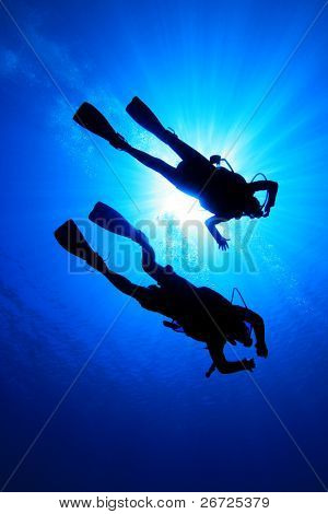 Couple scuba diving, silhouetted against sun