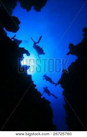 Scuba Divers descend into an underwater cavern