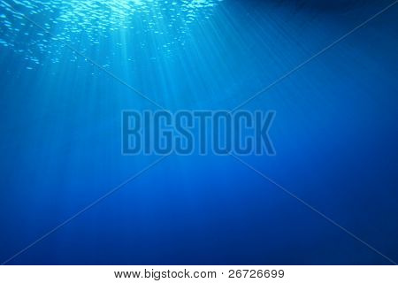 Abstract background of sun rays in clear blue water
