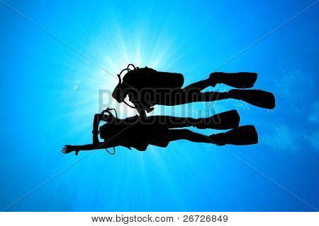 Scuba Divers: Student and Instructor silhouetted against Sunburst