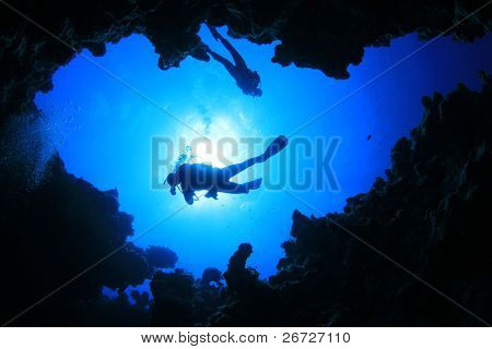 Scuba Divers descend into an Underwater Cavern. Silhouettes against sunburst