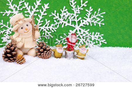Cute snowman figure in snow with three santa claus figures - christmas decoration