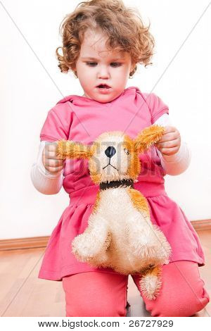 little girl playing with her favorite stuffed animal  at home