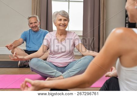 poster of Senior couple with trainer sitting in lotus position meditating. Instructor with old man and elderly