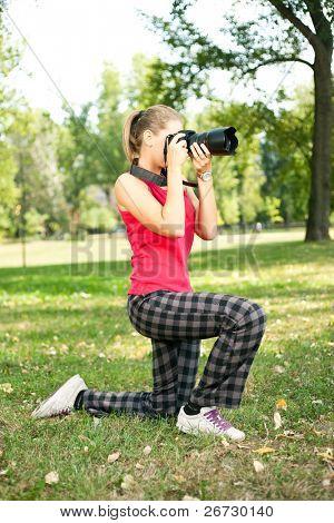 Girl holding eine Kamera, ein Bild im Freien, schießen sie sucht durch Kamera