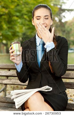 tired businesswoman yawning on cafe break in park