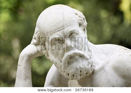 Thoughtful statue on blurry background in Villa Giulia, Palermo, Italy