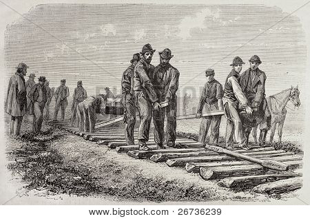 Antique illustration of  workers setting rails of the Union Pacific Railroad. Original, from drawing of Duvaux, was published on L'Illustration, Jounrnal Universel, Paris, 1968