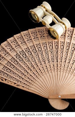 Old white and gold opera glasses and wooden fan isolated on black.