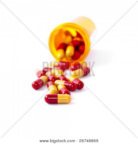 Pills spilling out of pill bottle isolated on white. Shallow depth of field. Focus on the closest pill.