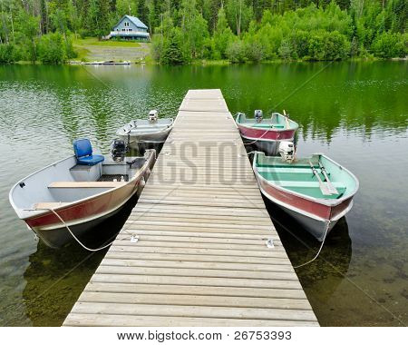 Boats on lake over a waterfront house.