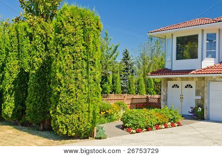 Fragment of a nice house and green frontyard at sunny day in Vancouver, Canada.