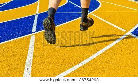 Füße eines laufenden Menschen über bunte Laufbahn