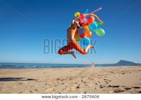 Girl With Colorful Balloons Jumping On The Beach