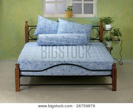 Studio shot of room interior with queen size bed.