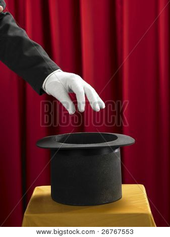 Hands of the magician with top hat on stage.