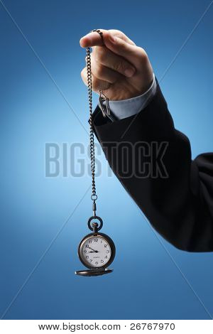 Human hand swinging a pocketwatch.