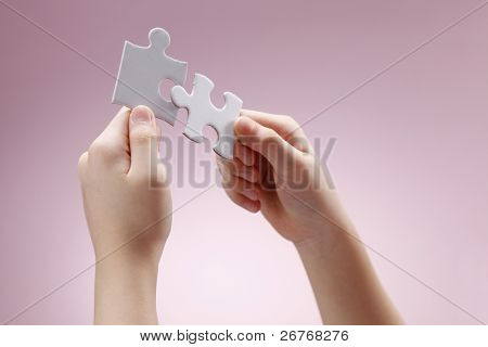 Human hand holding two puzzle pieces.