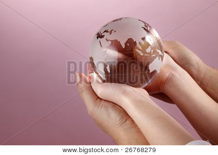 Two people holding a glass globe.
