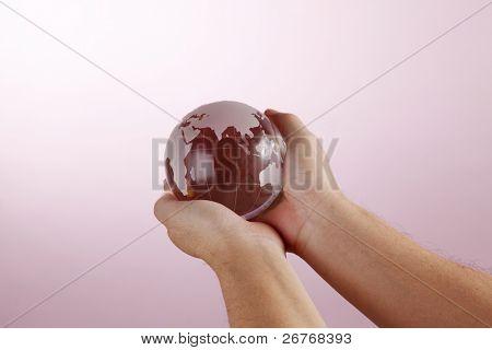 Human hand holding globe on pink background.