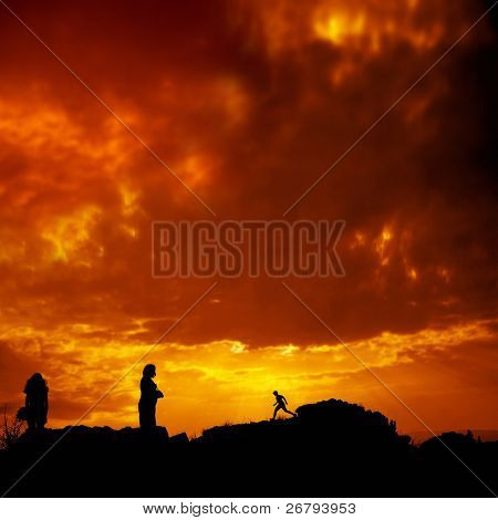 people silhouetted by sunset over orange background