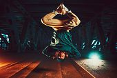 Young cool man break dancer jumping upside down. Urban bridge with cool and warm lights background. poster