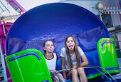 Two cute teen girls playing and having fun while riding an amusement park ride. Sticking out their t poster