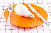Lamp On Orange Dish, Power Consumption Concept, Selective Focus poster