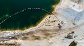 Aerial view of machinery and mine equipment near deep blue lake on sandy surface poster