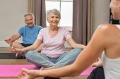 Senior couple with trainer sitting in lotus position meditating. Instructor with old man and elderly poster