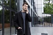 Photo of stylish man 20s talking on cell phone while walking outdoor near glass building poster