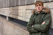Young adult male teenager boy outside in an urban city wearing a green parka coat leaning against a  poster