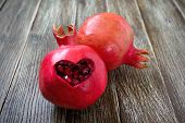 Ripe Pomegranate Fruit Close Up On Wooden Background. Healthy Eating Concept. Cut In The Shape Of A  poster