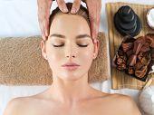 Head massage. Masseur doing massage the head of woman in a spa salon. poster