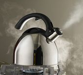 Close up shot of steaming tea kettle. Heater glow under the kettle.